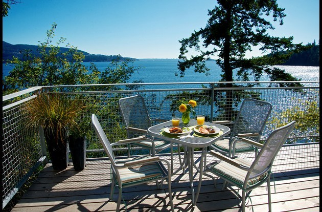 waterfront sun deck with expansive ocean views, patio dining, and briquette BBQ