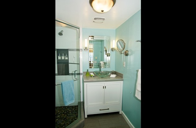 NEWLY RENOVATED washroom with walk in shower with a pebble floor, LED lighting, and cotton linens.